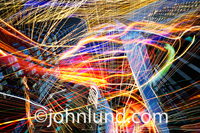 This is a picture of communication technology and social networking represented by streaks of multi-colored lights exploding in, around and through urban high rise buildings.