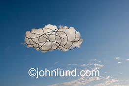 Security and cloud computing are visually illustrated in this photo of a cloud wrapped in barbed wire against a background of blue sky.