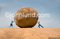 Concept stock photo of a man and a woman each pushing on different sides of a boulder illustrating conflict and struggle.