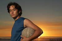 Man holding a volleyball on the beach at sunset. He has the ball under his left arm and is looking over his left shoulder towards the camera.