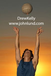 Picture of a Man with his arms stretched out above his head serving a volleyball. The volleyball has just left his hands. Beautiful orange sunset behind the man.  Action volleyball shot.