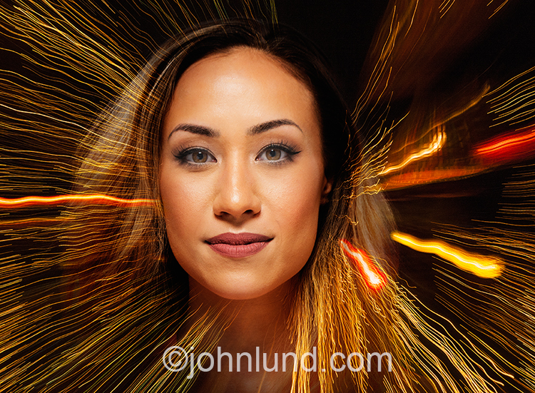 A beautiful woman is combined with streaks of light to create a colorful stock photo illustrating concepts such as communications technology, powerful women, and the future.