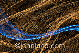 Big data transmissioin is represented in this stock photo showing streaks of blue light transversing a complex and intricate network of golden light.