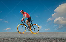 A cyclist speeds down a road with his wheels on fire in a stock photo about speed, determination and effort.
