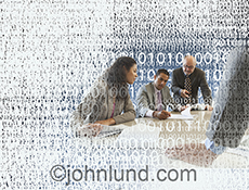 Four people engage in a business meeting surrounded by digital numbers in a stock photo about business in the digital age.