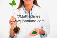 Photo of a woman in a lab coat holding a plant with roots in one hand and a handful of green pills in the other hand.  Represents bio research and homeopathic medicines.