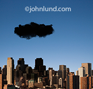 A black cloud hovers over a city in a stock image about the dangers, risks, and challenges of online and cloud computing.