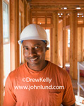 Black contractor in a white hard hat is smiling and facing the camera. The man is wearing an orange T-shirt with a pocket and in the background is the framing for a new home. Pictures of hard working black men for ads.