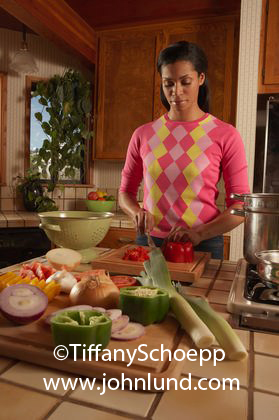 Picture of a black woman preparing a healthy meal for her family. The counter is covered with fresh produce, peppers, onions, leeks, and more.  Helathy living and lifestyle pictures for advertising and advertisements.
