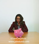 Picture of a black woman executive sitting at a table with a large pink piggy bank sitting on the table in front of her. She is leaning her arms on the table and staring at the piggybank.  Pink piggybank photos.