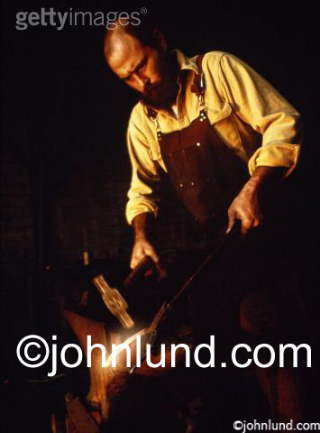 Stock photo of a blacksmith at work using a hammer to beat a horse shoe into shape on an anvil.
