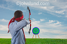 An archer wears a a red blindfold as he draws back his arrow and points in the direction of a target in a business concept image about information, skill and confidence.