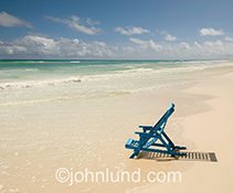 A solitary blue deck chair sits on a white sand beach at the edge of the waves of a tropical sea in this stock image about getting away from it all, vacations, solitude and travel.