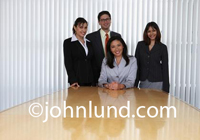 Board Room Executive Portrait. Four business executives, 3 women and one man in the board room having their photo taken.  Business people pic.