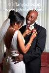Picture of a Bride and Groom of African descent putting on the groom's boutonniere.  The couple is happy and smiling on their wedding day. Wedding pictures of a happy black couple.