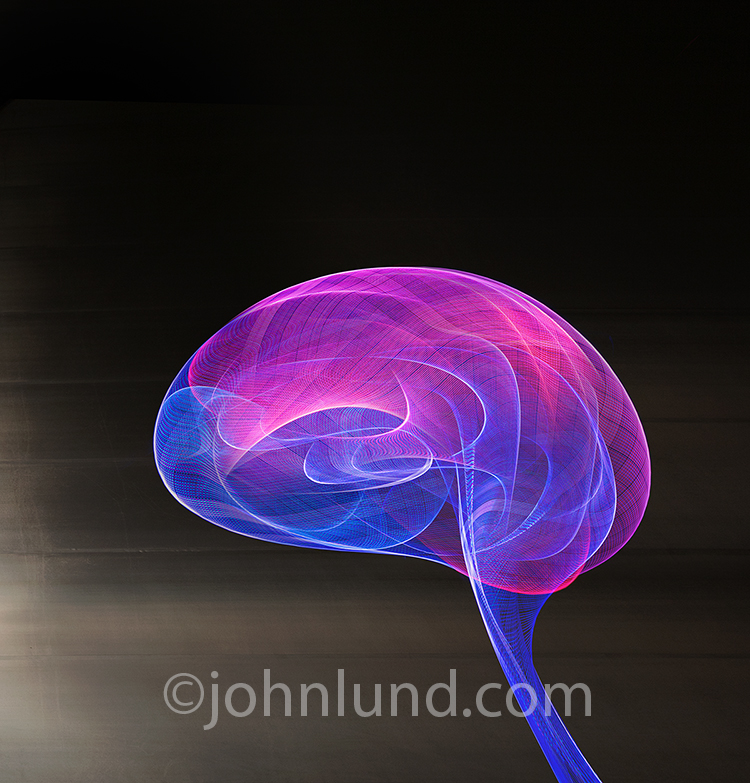AI, brain research, and science are all represented in this stock photo of a human brain formed from blue and magenta light trails against a dark metallic background.