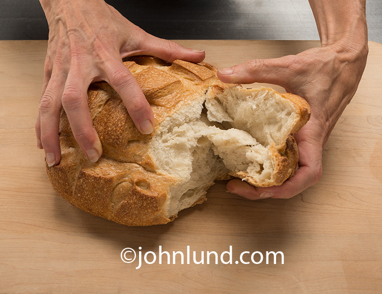 "A pair of hands are literally ""breaking bread"" in this photographic metaphor for friendship, connection and community."