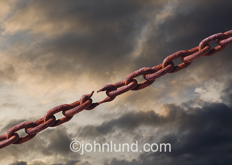 A breaking point is illustrated by this stock photo of a rusty chain with a weak link stretched to the point of failure against a backdrop of stormy clouds.