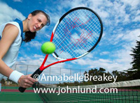 Funny picture of a tennis playing woman holding her racket with a hold right through the center. Broken strings in a tennis racket.  Cloudy blue sky. Green tennis ball in front of the racket.  Funny sports pictures for advertising.