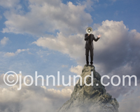 A businessman stands on a mountain peak and broadcasts his message through a megaphone or loudspeaker as he rants.