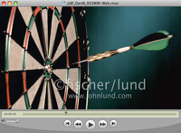 A dart slides through the air and strikes the center of a bullseye in a dartboard in this concept stock video clip