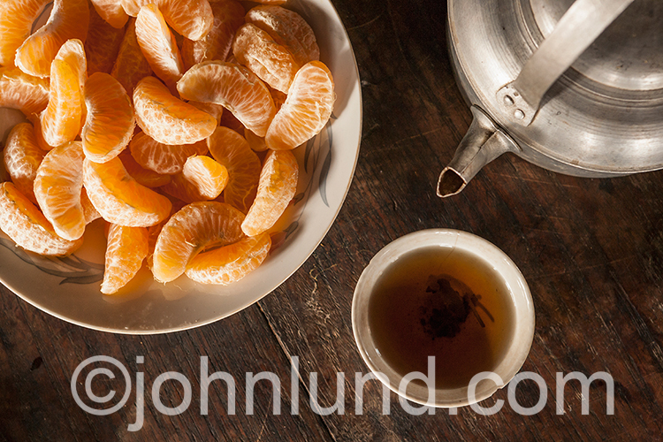 Tangerine segments, a tea pot, and a cup of tea are the elements making up this detail stock photo of travel and vacations in Myanmar or Burma.