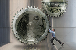 A businessman pushes on huge money gears in a stock photo about business infrastructure and financial incentives.