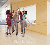 Business success and teamwork are the unmistakable concepts illustrated in this image of five people, in a corporate environment, engaging in an energetic high five celebration.