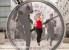 Three business people run through an urban environment with a stopwatch superimposed over the photo in an image about fast paced business, deadlines and competition.