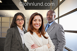Two businesswomen and a businessman stand together in an office in a display of business teamwork.