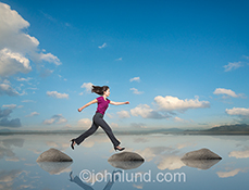 A woman strides confidently across a body of water stepping from rock to rock in an image about women in business, challenge and success.