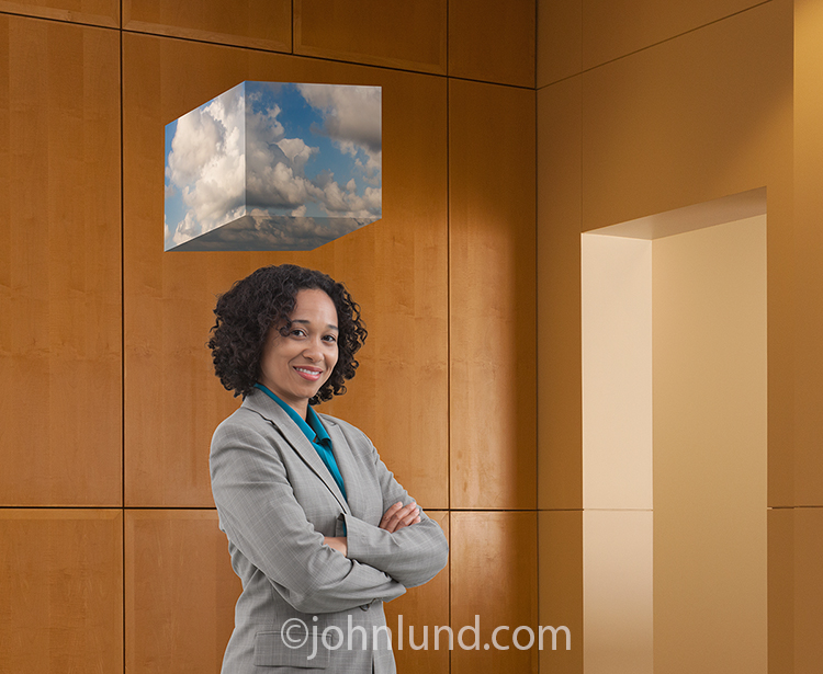 "A businesswoman is connected to the cloud in this stock photo of a woman dressed in business attire and standing beneath a ""cube"" of clouds, in a  corporate business lobby."