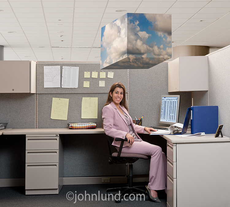 "Successful cloud computing is illustrated in this stock photo of a smiling businesswoman sitting in her office beneath a ""cube"" of clouds."