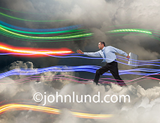 Streaks of colored light trails arc through a cloud bank as a businessman marches forward through the mist, briefcase in hand in a stock photo about cloud computing, connections, and networking.