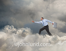 A businessman strides through a cloud bank, briefcase in hand, in a stock photo about accessing the cloud, cloud computing, connections and online computing.