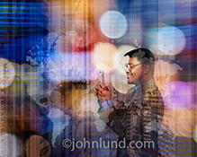 A businessman stays globally connected in a dynamic and colorful stock photo featuring a man using his mobile device agains a composite background of urban buildings, city lights at night, and a map of the continents.