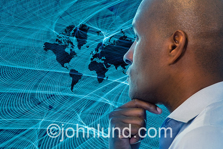 An African American businessman contemplates a global map immersed in streaking blue lights representing networking and future communications technology.