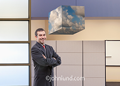 Cloud computing in an office setting is illustrated in this stock photo of a smiling businessman in a high tech office standing next to a