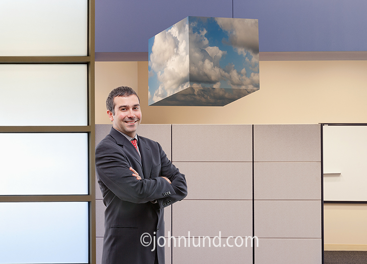"Cloud computing in an office setting is illustrated in this stock photo of a smiling businessman in a high tech office standing next to a ""cube"" of clouds indicating access to the cloud, opportunity, and successful online computing."