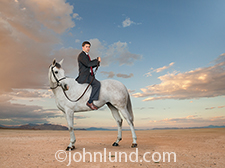 A perplexed and fearful businessman sits astride a horse, backwards, in a humorous image about ineptitude, the need for training, and a lack of preparation.