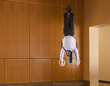 A businessman performs on the gymnastic rings in a high end corporate office in a stock photo about the business performance and skill required for success and achievement.