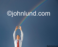 A business man holds up his hands to catch a rainbow showing success, possibilities and a bright future. A rainbow is symbolic of reward, luck and success.
