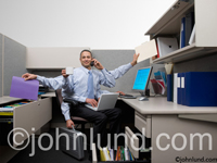Picture of  multi-tasking businessman. A business man multi tasking in his office cubicle using six arms to simultaneously perform functions. Photo of a businesman with mutliple sets of arms.