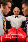Funny pictures of people. This funnny people picture depicts two men in dress shirts and ties standing in a boxing ring face to face and wearing big red boxing gloves. Silly photo of men boxing.  Humorous advertising pics for small businesses.