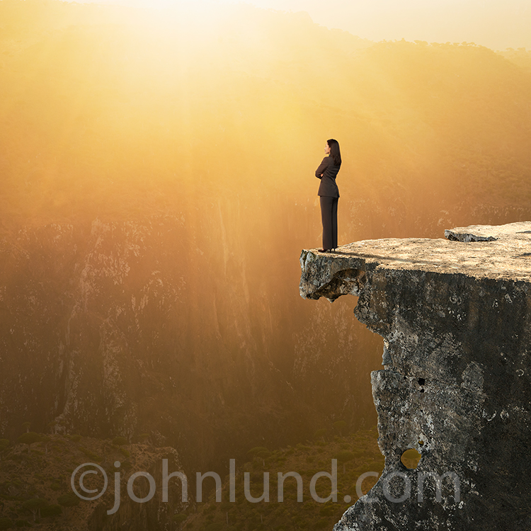 A businesswoman stands at the edge of a cliff gazing off into a golden sunset as she contemplates the future in a stock photo about the way forward, decisions, leadership and women's issues.