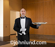 A butler stands at the ready holding an empty silver tray in this concept image about excellent service.