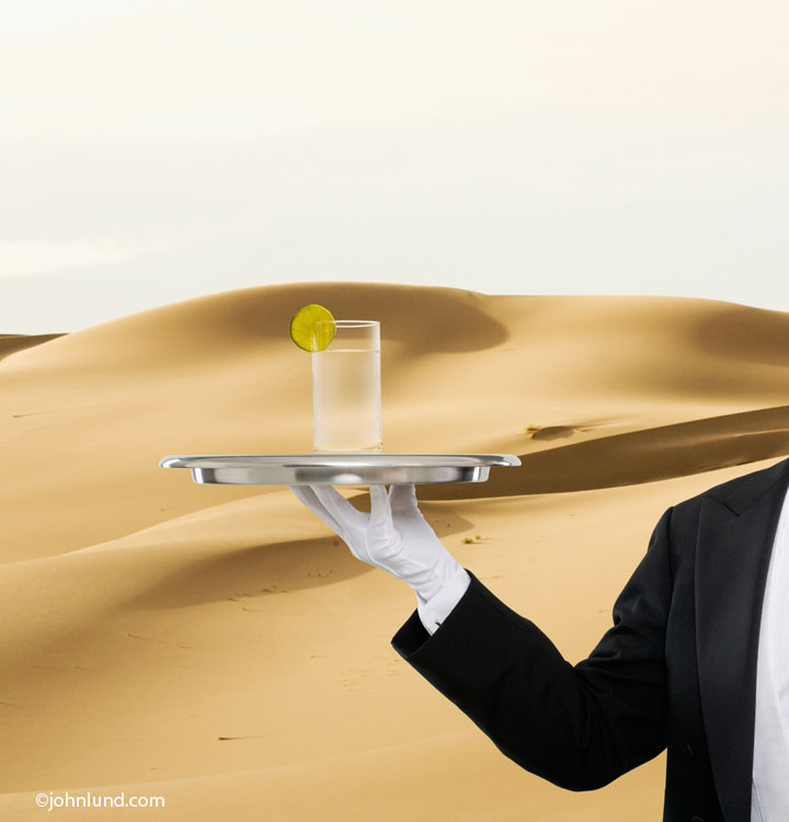 The stark contrast between an ice-cold drink and the hot, dry, parched desert is displayed in this concept stock photo of a bulter holding a silver tray with a cold drink on it in a desert environment.