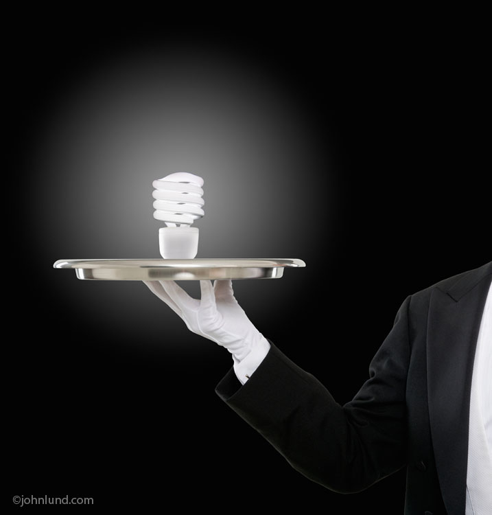 An energy saving light bulb is offered on a silver tray by a butler in an image about energy, conservation and service.