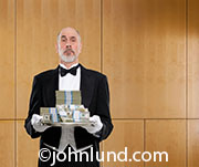 A stack of money is being offered on a silver tray by this butler in a visual metaphor for success, abundance, capital infusion and financial service.