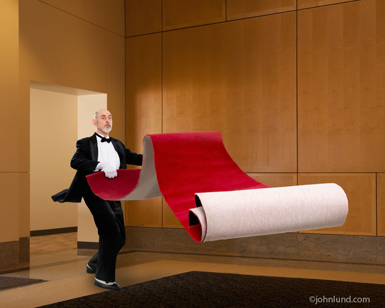 A butler rolls out a red carpet in a picture metaphor for great service and luxurious preferential treatment, and the rewards of success and achievement.